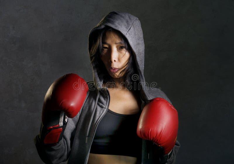Закройте вверх по портрету пригонки детенышей и здоровой азиатской китайской женщине боксера в перчатках hoodie и бокса верхней ч стоковое фото