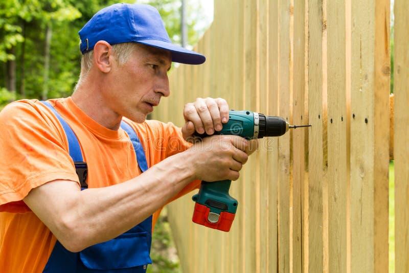 Закройте вверх по портрету работника, устанавливая деревянную загородку стоковая фотография