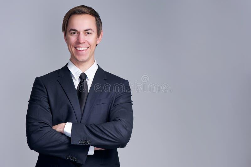 Закройте вверх по портрету расслабленного бизнесмена усмехаясь при пересеченные оружия стоковые изображения rf