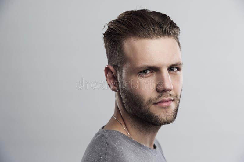 Закройте вверх по портрету серьезного хмурого бородатого человека при стильный стиль причёсок представляя против белой предпосылк стоковое изображение rf