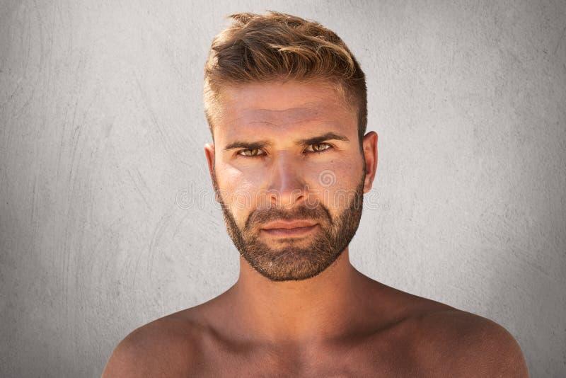 Закройте вверх по портрету симпатичного мужчины при темные глаза, щетинка и ультрамодный hairdo быть нагой, смотрящ с серьезным в стоковая фотография rf