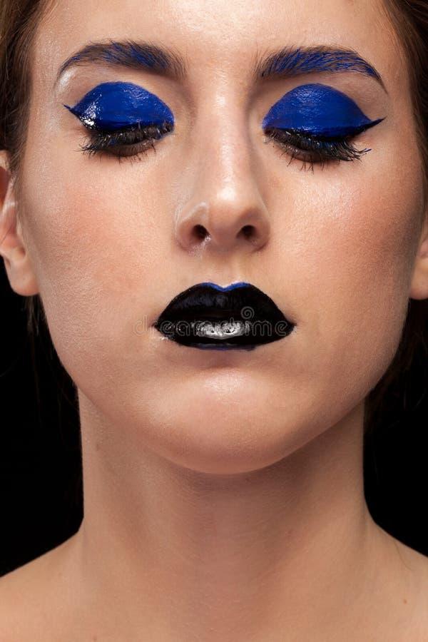 Закройте вверх по портрету сини женщины нося составьте с черными губами стоковое изображение rf