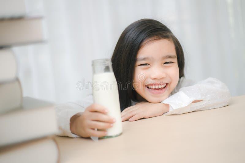 Закройте вверх по портрету стекла o прелестной маленькой азиатской девушки выпивая стоковая фотография