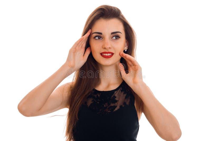 Закройте вверх по портрету стильной молодой женщины с красными губами в черном платье смотря прочь изолированный на белой предпос стоковая фотография rf