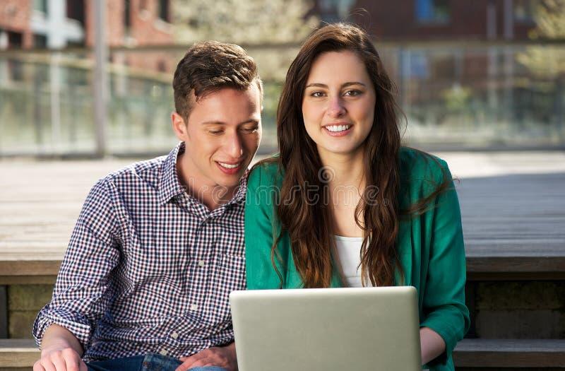 Закройте вверх по портрету 2 студентов колледжа работая на компьтер-книжке outdoors стоковые фото