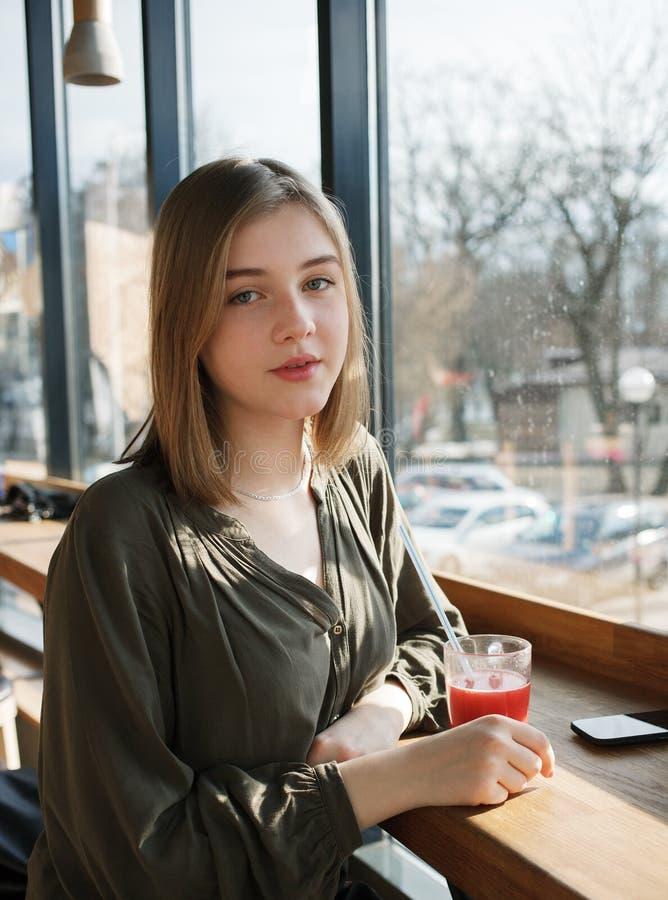 Закройте вверх по портрету счастливой красивой предназначенной для подростков девушки студента с стеклянным чаем плодоовощ соломы стоковые фотографии rf
