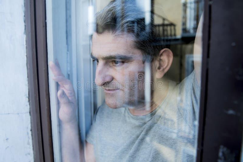 Закройте вверх по портрету унылого и подавленного человека 40s смотря через w стоковое фото rf