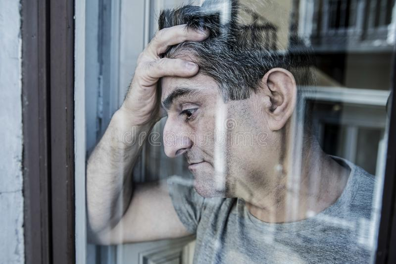 Закройте вверх по портрету унылого и подавленного человека 40s смотря через w стоковое изображение rf