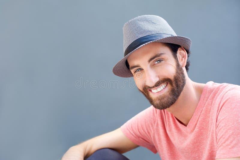 Закройте вверх по портрету усмехаясь молодого человека с шляпой стоковая фотография rf