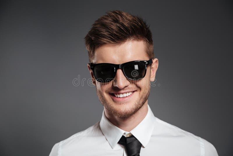 Закройте вверх по портрету усмехаясь стильного человека в солнечных очках стоковое фото rf