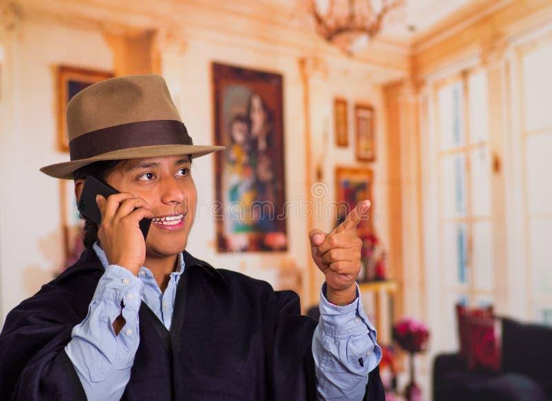 Закройте вверх по портрету шляпы и плащпалаты молодого индигенного человека нося используя сотовый телефон стоковое изображение rf