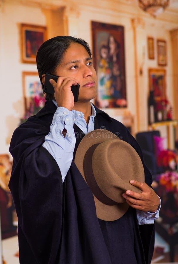 Закройте вверх по портрету шляпы и плащпалаты молодого индигенного человека нося используя сотовый телефон стоковое фото