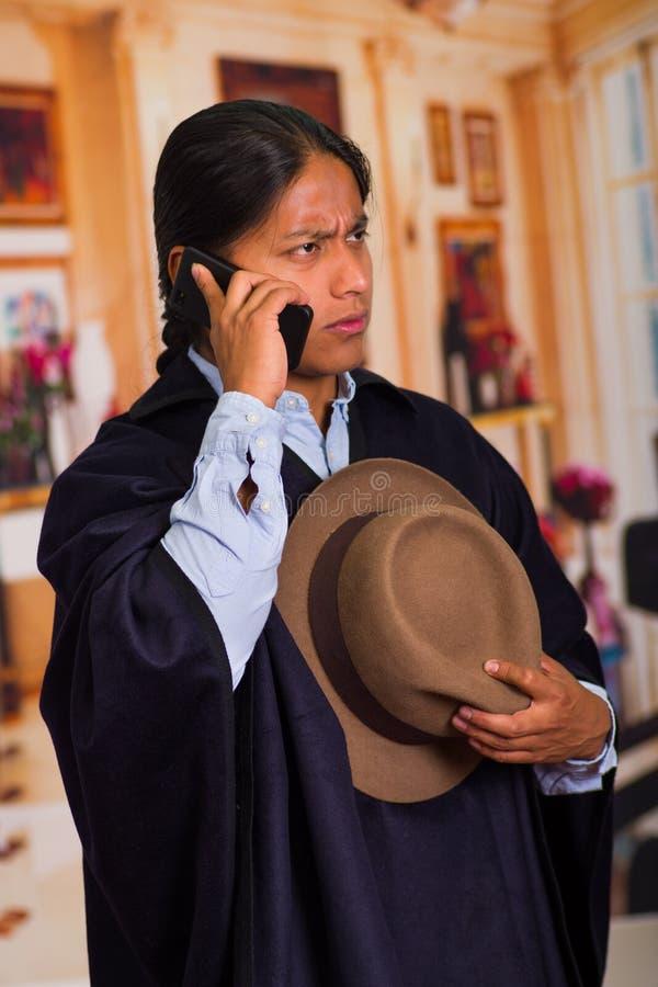 Закройте вверх по портрету шляпы и плащпалаты молодого индигенного человека нося используя сотовый телефон стоковые изображения rf
