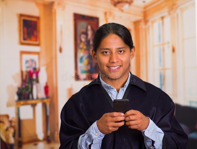 Закройте вверх по портрету шляпы и плащпалаты молодого индигенного человека нося используя сотовый телефон стоковые изображения