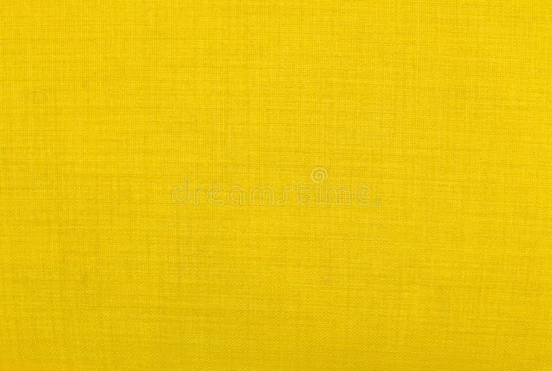 Закройте вверх по предпосылке желтой текстуры ткани стоковое фото