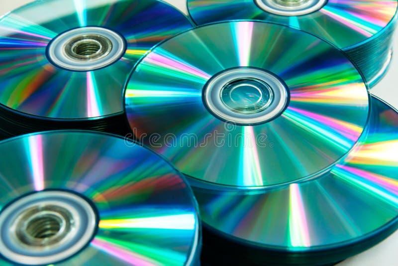 Закройте вверх по предпосылке КОМПАКТНОГО ДИСКА и DVD стоковое фото rf