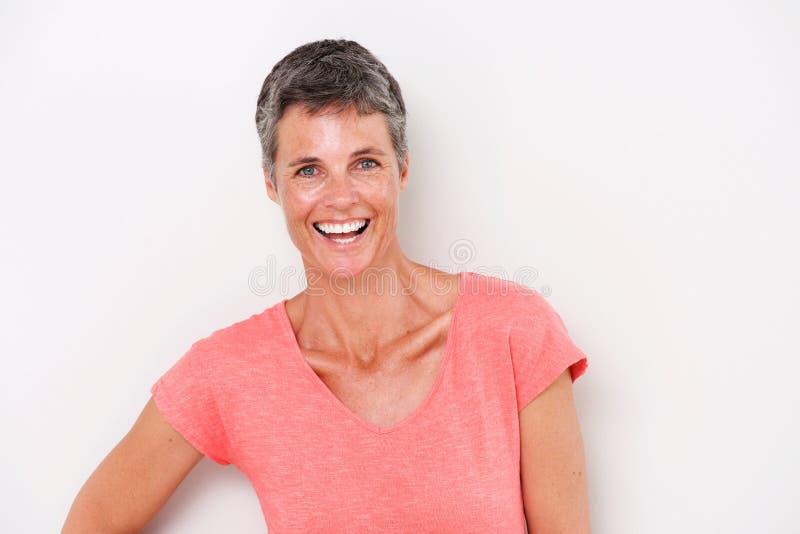 Закройте вверх по привлекательной женщине среднего возраста смеясь над белой предпосылкой стоковые фото