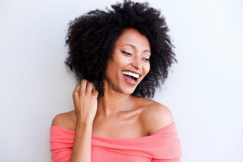 Закройте вверх по привлекательной молодой чернокожей женщине смеясь над против белой предпосылки стоковые фотографии rf