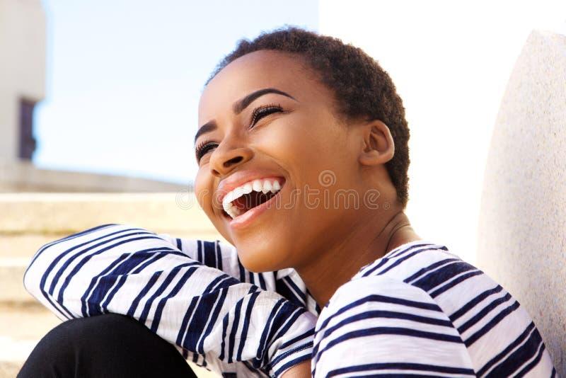 Закройте вверх по привлекательной молодой чернокожей женщине смеясь над снаружи стоковое фото