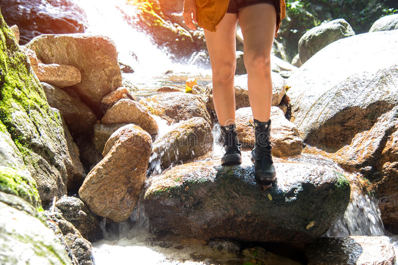 Закройте вверх по прогулке женщины hiker ноги азиатской путь в падении воды, лесе предпосылки стоковое фото rf