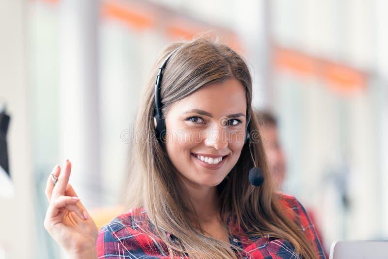 Закройте вверх по плану усмехаясь коммерсантки в центре телефонного обслуживания стоковая фотография