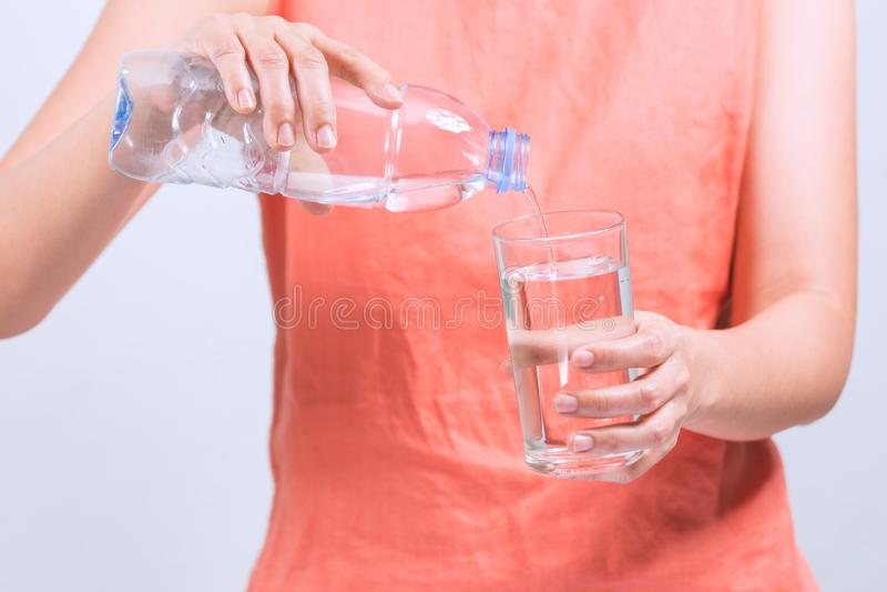 Закройте вверх по рукам женщина льет воду бутылки стоковое изображение