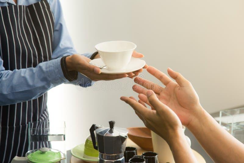 Закройте вверх по рукам клиента сервировки штата в кофейне стоковые изображения rf
