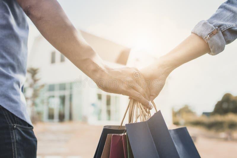 Закройте вверх по рукам пар влюбленности держа хозяйственную сумку для того чтобы самонавести, conc стоковая фотография rf