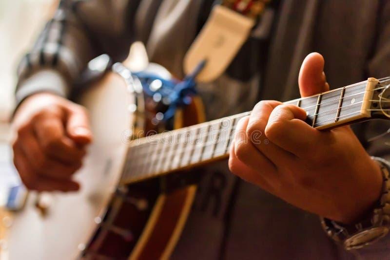 Закройте вверх по рукам человека играя банджо стоковые фотографии rf