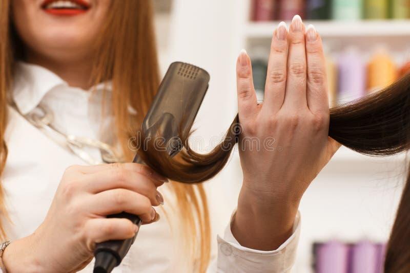 Закройте вверх по рукам ` s парикмахера с уловкой стоковое изображение