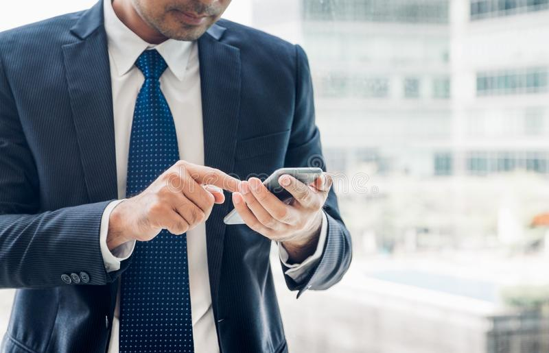 Закройте вверх по руке бизнесмена используя мобильный телефон около ветра офиса