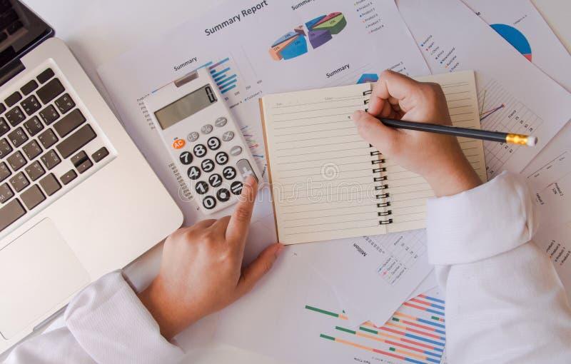 закройте вверх по руке бизнес-леди взгляд сверху используя калькулятор и lapto стоковое изображение rf