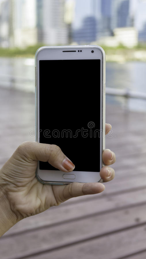Закройте вверх по руке держа телефон на запачканной предпосылке городского пейзажа стоковые фотографии rf