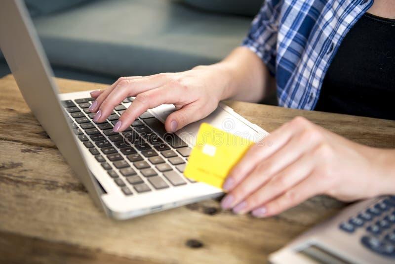 Закройте вверх по руке женщины держа покупки кредитной карточки на линии или банк на интернете с портативным компьютером дома в о стоковое изображение