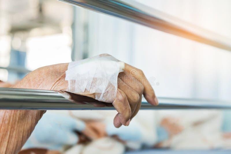 Закройте вверх по руке пожилого пациента с внутривенным катетером для впрыски заткните внутри руку стоковое изображение