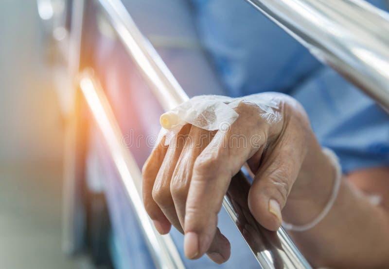 Закройте вверх по руке пожилого пациента с внутривенным катетером для впрыски заткните внутри руку стоковое изображение rf