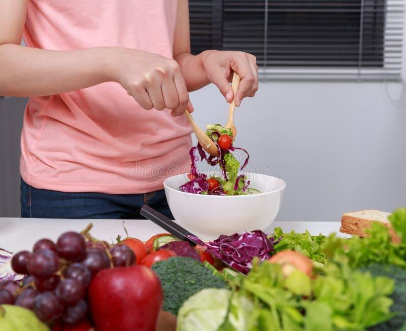 Закройте вверх по салату женщины смешивая пока варящ в кухне стоковые фото