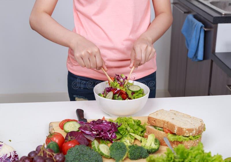Закройте вверх по салату женщины смешивая пока варящ в кухне стоковое изображение