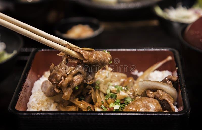 Закройте вверх по свинине гриля с луком и чесноком в еде японца boxet стоковые изображения rf