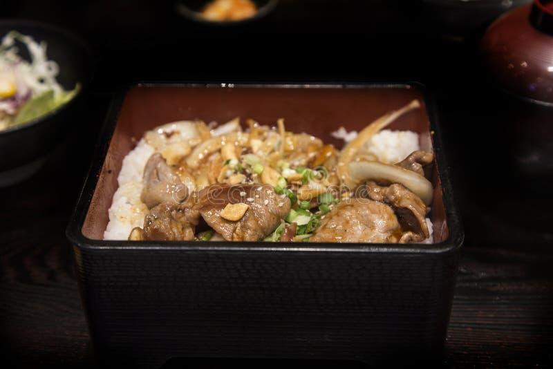Закройте вверх по свинине гриля с луком и чесноком в еде японца boxet стоковая фотография