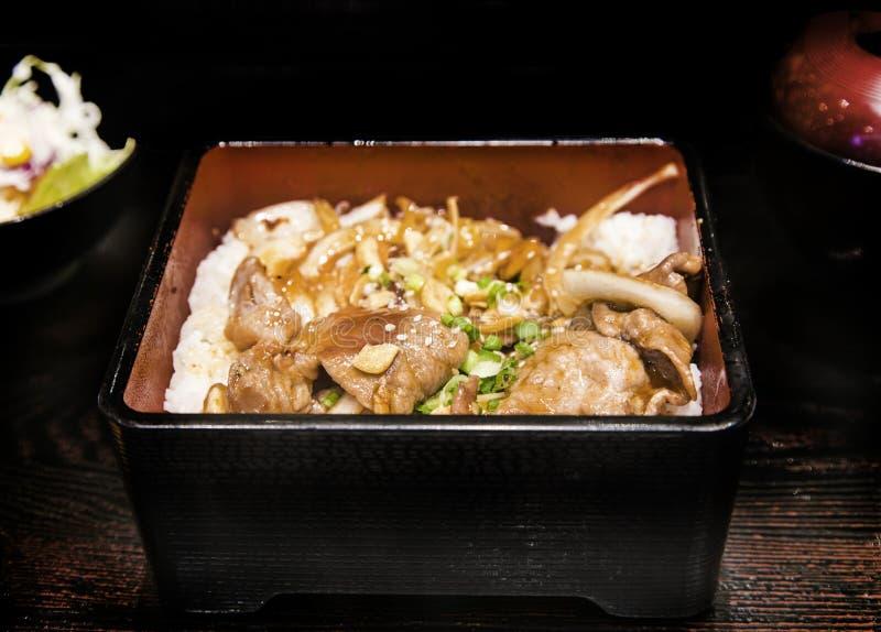 Закройте вверх по свинине гриля с луком и чесноком в еде японца boxet стоковое фото rf