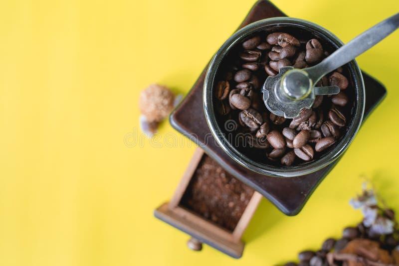 Закройте вверх по селективным кофейным зернам и grinned кофейному зерну в винтажном деревянном механизме настройки радиопеленгато стоковая фотография rf