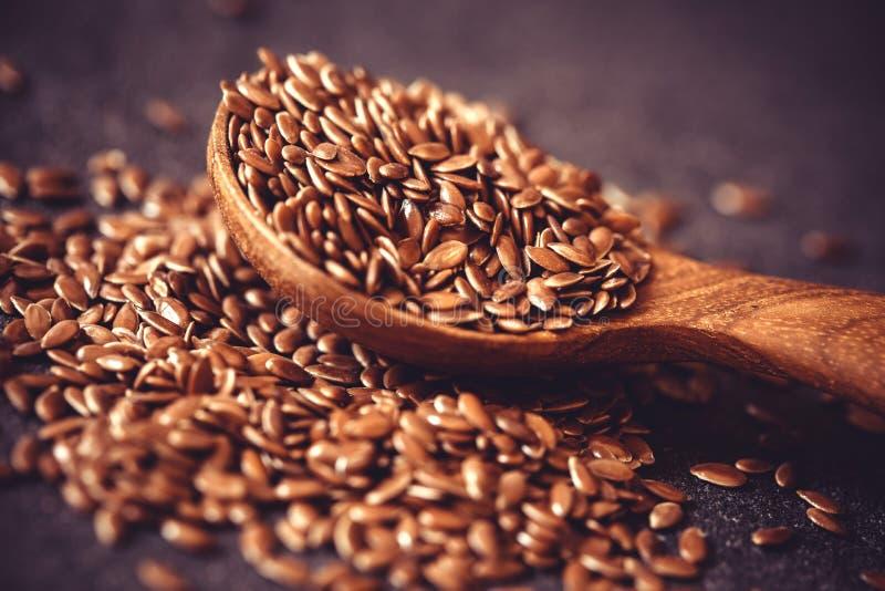 Закройте вверх по семени льна в деревянной ложке, супер еде с высотой a стоковое фото rf