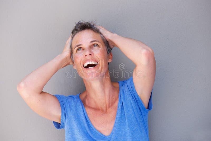 Закройте вверх по смеясь над женщине с руками в волосах стоковые фото