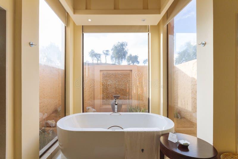 Закройте вверх по современному району ванной комнаты с ванной внутрь в утре на Абу-Даби, ОАЭ стоковые фото