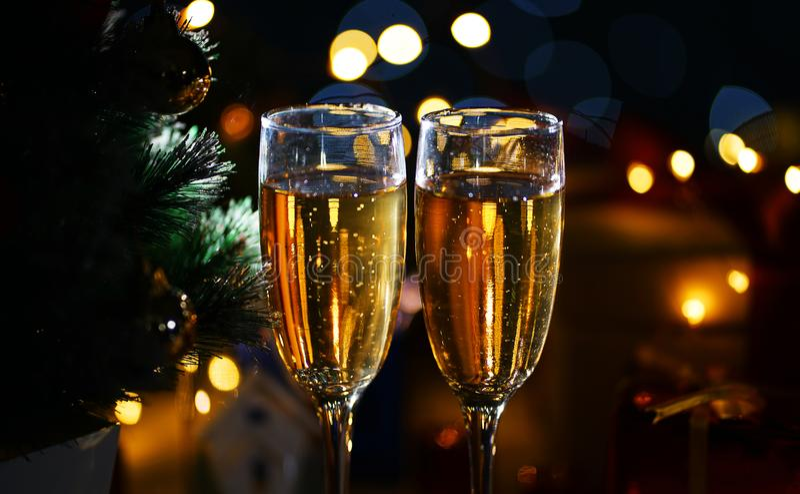 Закройте вверх по 2 стеклам Шампани около рождественской елки Темнота почти стоковая фотография
