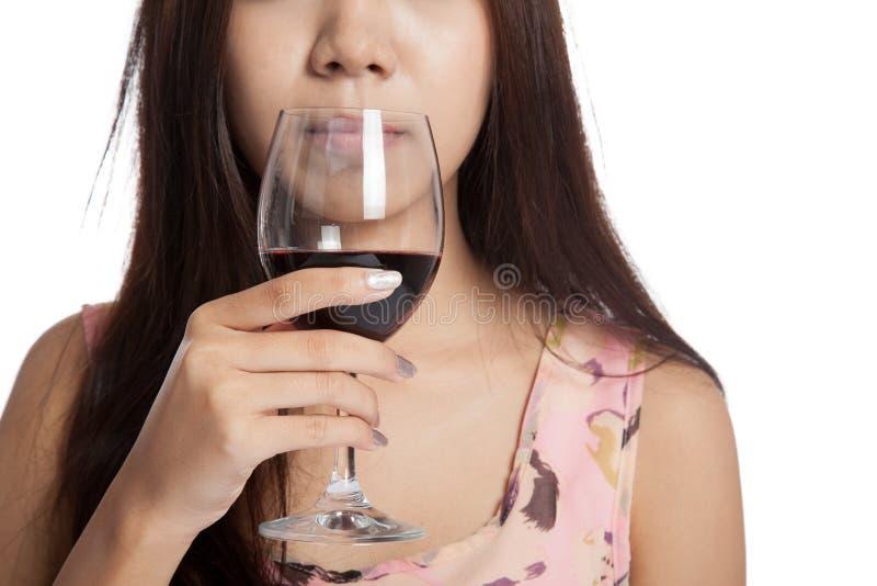 Закройте вверх по стеклу красного вина в азиатской руке женщины стоковое фото