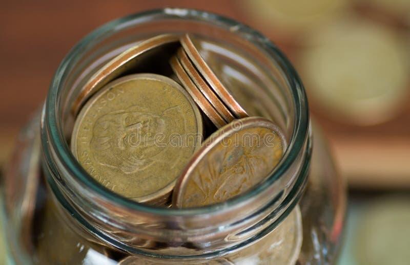 Закройте вверх по стеклянному отверстию опарника заполненному вверх с монетками доллара стоковое фото