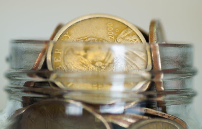 Закройте вверх по стеклянному отверстию опарника заполненному вверх с монетками доллара стоковая фотография