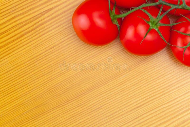 Закройте вверх по студии снятой пука томатов на деревянном столе стоковые изображения